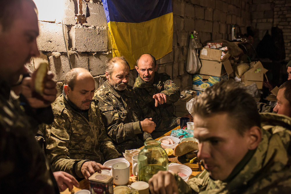 PISKY, UKRAINE - NOVEMBER 17, 2014: Members of the Ukrainian army share a meal inside the abandoned building being used as their base in the fight against pro-Russia rebels for control of the Donetsk airport, in Pisky, Ukraine. CREDIT: Brendan Hoffman for The New York Times