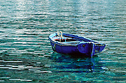 """A blue oar boat floats in the green Mediterranean Sea, at Loutro harbor, Crete, Greece, Europe. Published in """"Light Travel: Photography on the Go"""" book by Tom Dempsey 2009, 2010."""