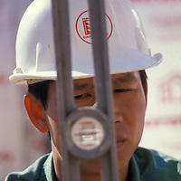 Construction worker Thanh Tan Nguyen eyes a level at an Alexandria, VA construction site. Release available.