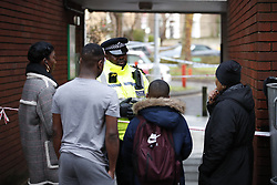 © Licensed to London News Pictures. 06/02/2019. London, UK. Friends of the victim's family talk to a police officer near the crime scene on Westbridge Road in Battersea where a 19 year old man was fatally stabbed last night. Police have arrested two men. Photo credit: Peter Macdiarmid/LNP