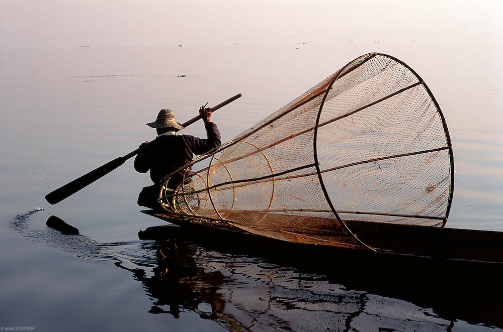 — In the early morning, fishermen ply the waters of Inle Lake, looking for favorable spots to fish.