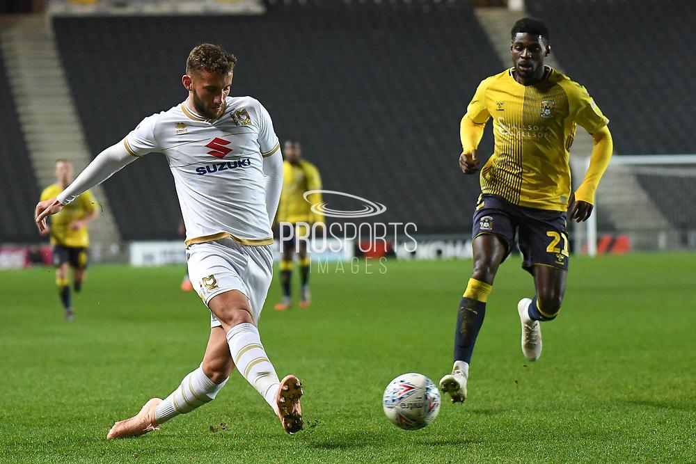 Milton Keynes Dons midfielder Jordan Houghton (24) on defensive duties  under pressure from Coventry City striker Amadou Bakayoko (21) during the EFL Trophy match between Milton Keynes Dons and Coventry City at Stadium:MK, Milton Keynes, England on 3 December 2019.
