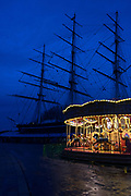 The carousel near the Cutty Sark glows in the winter twilight, with the Cutty Sark silhouetted behind; Greenwich, London.