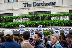 © Licensed to London News Pictures. 06/04/2019. LONDON, UK.  Members of the LGBT community stage a protest outside the Brunei-owned Dorchester Hotel in reaction to reports that the Sultan of Brunei decreed that adultery and gay sex is punishable by death by stoning in the Islamic sultanate.  Several large clients of the Dorchester Hotel have already ceased bookings in response to the decree.  Photo credit: Stephen Chung/LNP