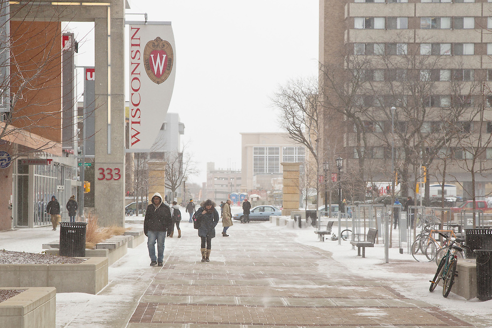 Pedestrians make their way along the East Campus Mall at the University of Wisconsin-Madison, passing the University Square building on the left and residence halls on the right in Madison, Wis., Feb. 10, 2012. (Photo © Andy Manis)