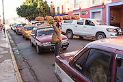 A worker carries trays of Pan de Muerto a special sweet bread for celebrating the Day of the Dead festival through traffic at Central de Abastos Market October 28, 2014 in Oaxaca, Mexico.