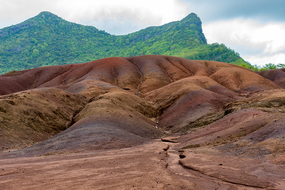 Green mountains rise in the background of the seven colored earths in Chameral, Mauritius, created by a cooling volcano.