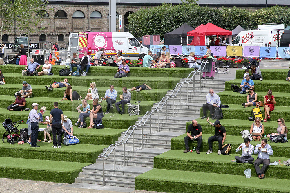 © Licensed to London News Pictures. 17/07/2019. London, UK. People enjoy the warm weather in Granary Square near Kings Cross in central London. According to the Met Office, rain is forecast across the country during the next few days. Photo credit: Dinendra Haria/LNP