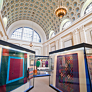 Display case in the Lancaster Quilt and Textile Museum in the historic downtown section of Lancaster, Pennsylvania. The museum specializes in Amish quilts from the nearby region. Lancaster is the hub of Pennsylvania Dutch Country (also known as Amish community). The building housing the museum was formerly an historic bank and it retains the large bank vault, which now contains a