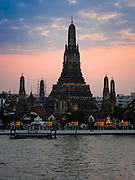 "19 DECEMBER 2013 - BANGKOK, THAILAND:  Wat Arun at the end of the day. Wat Arun Ratchawararam Ratchawaramahawihan or Wat Arun (""Temple of Dawn""), a Buddhist temple (wat) in Bangkok Yai district of Bangkok, on the Thonburi side of the Chao Phraya River. The temple derives its name from the Hindu god Aruna, often personified as the radiations of the rising sun. Wat Arun is among the best known of Thailand's landmarks and the first light of the morning reflects off the surface of the temple with pearly iridescence. Although the temple had existed since at least the seventeenth century, its distinctive Khmer style prang (spires) were built in the early nineteenth century during the reign of King Rama II.        PHOTO BY JACK KURTZ"