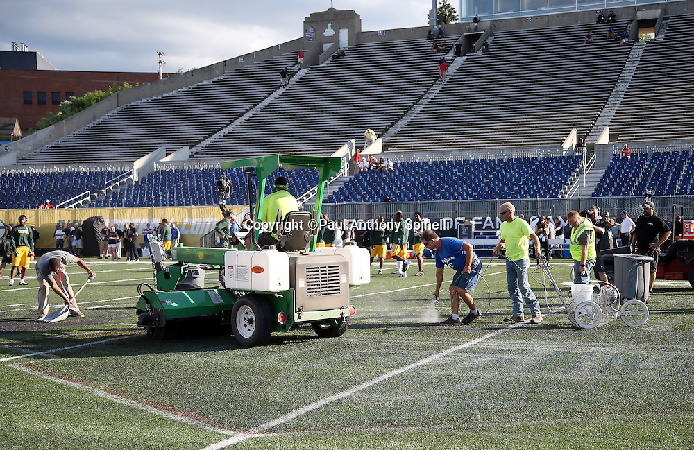 The grounds crew works at mid-field trying to remove a painted logo that caused footing problems with player cleats before the Green Bay Packers 2016 NFL Pro Football Hall of Fame preseason football game against the Indianapolis Colts on Sunday, Aug. 7, 2016 in Canton, Ohio. The game was canceled for player safety reasons due to the condition of the paint on the turf field. (©Paul Anthony Spinelli)
