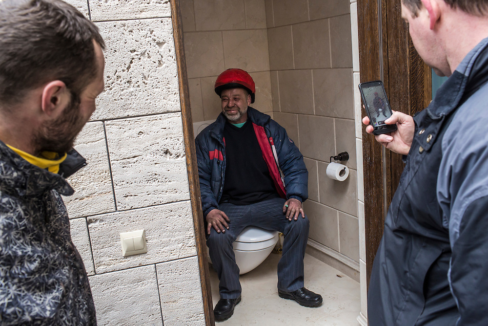 KIEV, UKRAINE - FEBRUARY 22: A man poses for a photo on a toilet at President Viktor Yanukovych's Mezhyhirya estate, which was abandoned by security, on February 22, 2014 in Kiev, Ukraine. After a chaotic and violent week, protesters took control of Kiev as President Viktor Yanukovych fled the city amid calls for his immediate resignation. (Photo by Brendan Hoffman/Getty Images) *** Local Caption ***