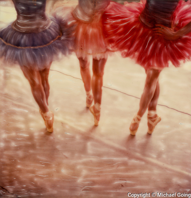 Three ballerinas wearing tutus en pointe