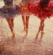 Three ballerinas wearing tutus en pointe
