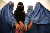 Four women voters at a polling booth in the ultra conservative Helmand capital Lashkar Gah display their ink-stained fingers indicating they have voted.