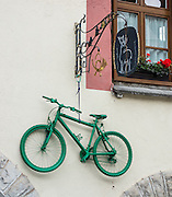 A green bicycle hangs as an ornament on a building, in Selva di Val Gardena, Dolomites, Italy, Europe. The beautiful ski resort of Selva di Val Gardena (German: Wolkenstein in Gröden; Ladin: Sëlva Gherdëine) makes a great hiking base in the Trentino-Alto Adige/Südtirol (South Tyrol) region of Italy, in the Dolomites, part of the Southern Limestone Alps, Europe. UNESCO honored the Dolomites as a natural World Heritage Site in 2009.