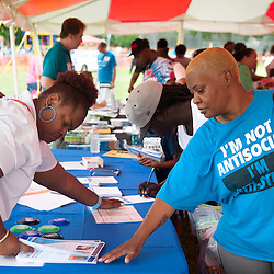 25 JULY 2015 -- FERGUSON, Mo. -- Participants gather information from non-profits and public service agencies during Convoy of Hope, a faith-based outreach program at Forestwood Park in Ferguson, Mo. Saturday, July 25, 2015. The event included health check ups, haircuts, career counseling, play areas for children, food for needy families and spiritual counseling.<br /> <br /> Photo by Sid Hastings.
