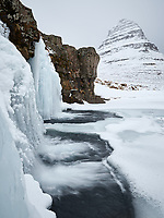 Kirkjufellsfoss waterfall in winter. Mount Kirkjufell in bakground. Snæfellsnes Peninsula, West Iceland.