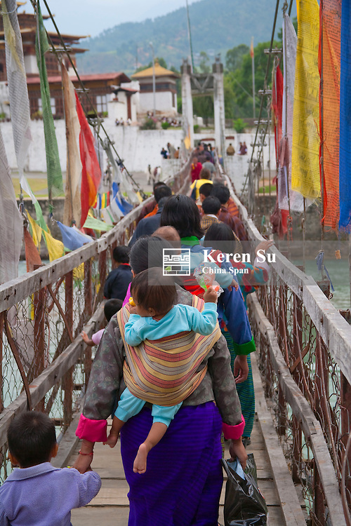 Pilgrims walk on suspending bridge to Punakha Dzong, Punakha, Bhutan