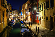 Venice, Italy, night #1. Boats line a canal at dusk. A tower in the distance, a walkway at right.