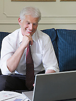 Business man using laptop sitting on sofa