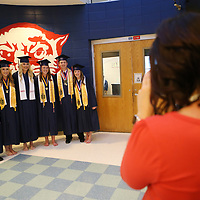 Baldwyn High School math teacher Blair Weaver, right, takes a photo of a group of seniors before the start of Friday night's graduation ceremony at the school.