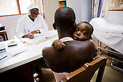 Kouadio Ahou Viviane holds her 16-month-old boy Emmanuel Ngora Kwame during a consultation with Sister Pauline Kangah Akissi and Dr. Charles Joseph Diby (not seen) at the NDA health center in Dimbokro, Cote d'Ivoire on Friday June 19, 2009.