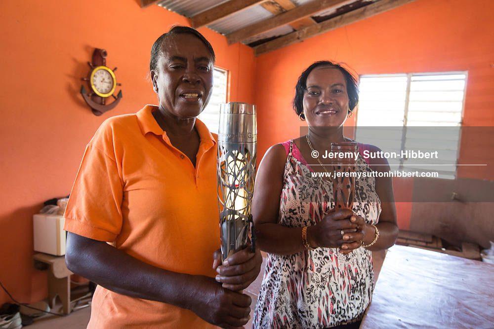 Almenna Cornelius (left) and Mareelyn Evelyn (who made replica pottery baton) with the Queen's Baton at Newcastle Pottery, in Nevis, in St. Kitts And Nevis, Saturday 29 March 2014.