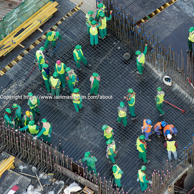 Migrant workers on construction site of high-rise  apartment skyscraper tower in Dubai United Arab Emirates