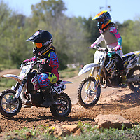 Lauren Wood | Buy at photos.djournal.com<br /> Maddix Lambert, 7, of Booneville, left, and Kenzye Brocato, 11, of Olive Branch ride their mini dirt bikes around the North Mississippi Motorsports race track Saturday, April 9 in Booneville.