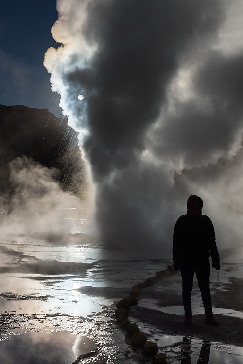 A woman stands in front of a big geyser at sunrise, Et Tatio geyser field, Chile.
