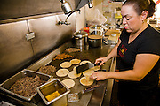 Lourdes Alvarez grills tortillas at her Mexican Restaurant, El Coyote in the suburb of Alsip, Chicago Illinois. (Lourdes Alvarez is featured in the book What I Eat;  Around the World in 80 Diets.)   MODEL RELEASED.