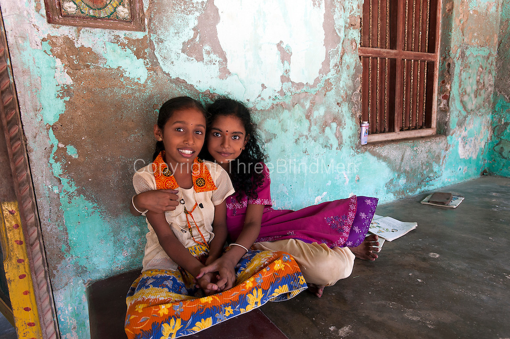 Two friends seated at the front of their home in Tarangambadi.