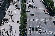 Viewed from the top of the Arc de triumph in the centre of Paris, the French capital, we see tiny human figures going about their daily business, a hurried frenzy of activity at street level far below. This street is the Avenue des Champs Elysees, one of the most famous of European boulevards and the multi-lane road that stretches away into the distance - from l'Etoile to Place de la Concorde - is dissected with zebra crossings over which more pedestrians negotiate the Parisian traffic that has stopped on a red light. Otherwise small figures walk along the pavement (sidewalk) and some disappear into an underground Metro entrance.