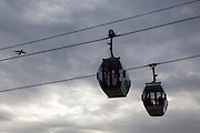 Two Emirates Air Line Cable Car ravel across the River Thames between Greenwich Peninsula and the Royal Docks in London, England, United Kingdom.  An Aeroplane passes by in the sky full of moody clouds.  The Air Line opened in 2012  and was built by Doppelmayr with sponsorship from the airline Emirates.  (photo by Andrew Aitchison / In pictures via Getty Images)