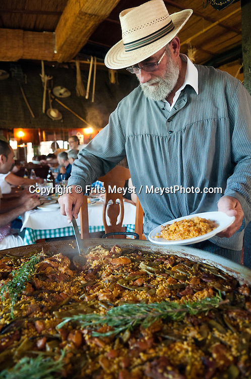 Valencia, Spain, September 2013. Eco Farmer and chef Toni Montoliu cooks a typical Valencian paella with rabbit and chicken over an open fire to serve the the guests of his reastaurant Barraca in Meliana, Horta Nord. In the middle of the Spanish Mediterranean coastline lies Valencia, a beautiful city backed by mountains and plains. The city itself is boasts beautiful architecture from the historic to avant-garde. Valencia is also famed for its art galleries and fabulous local cuisine, such as juicy Valencia oranges and traditional Spanish paella, which originated from here. A good way to explore the city is by bicycle. Photo by Frits Meyst