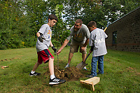 4th grade students Holden and Walter with the help of Eric Cardinal plant a tree and mount a plaque for the Liberty Elm Tree donated by Good Earth during their Day of Caring at Pleasant Street School on Thursday morning.  (Karen Bobotas/for the Laconia Daily Sun)