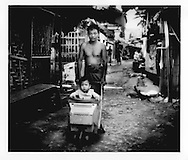 Karen refugee father pushes his son, born in the camp, in a stroller fashioned from a old television set, Mae La refugee camp, north of Mae Sot, Thailand.