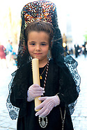 A little girl, in a Mantilla and black lace traditional dress, holds a candle at the start of a procession in Granada.