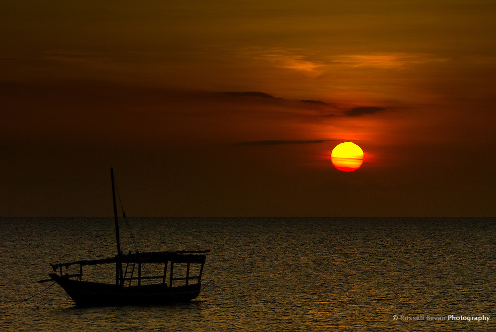 Silhouette of a dhow boat at sunset on Zanzibar