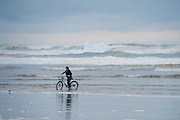 Woman on bicycle riding on edge of large waves crashing on the beach