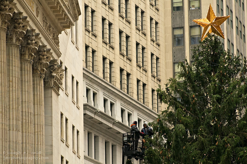 Workers string lights on Christmas tree outside New York Stock Exchange to prepare for lighting ceremony on December 4.
