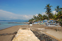 A scene of the beachfront of Candidasa in Bali, Indonesia.  Boats are pulled up on to the shore and the beach is ringed by palm trees.