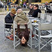 Belgie, Antwerpen, 8-10-2012Stadsgezicht, straatbeeld van deze stad in Vlaanderen. Kind maakt acrobatische bewegingen aan de stoel waar zijn vader op zit op een terrasjeFoto: Flip Franssen/Hollandse Hoogte
