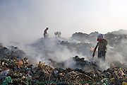Young child laborer boys are collecting recyclable material at the smokey Stung Meanchey Landfill in Phnom Penh, Cambodia.
