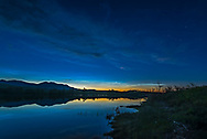 Noctilucent clouds glowing low in the north over the Waterton River at the Maskinonge picnic area in Waterton Lakes National Park, Alberta on June 17, 2018. Cassiopeia (the &ldquo;W&rdquo;) is at right. <br /> <br /> This is a high dynamic range stack of 5 exposures from dark to light, blended with Adobe Camera Raw. Taken with the Nikon D750 and Sigma 20mm lens. Additional contrast enhancement applied using Zone System Express 5 Photoshop extension and &ldquo;Enhanced Contrast&rdquo; function.