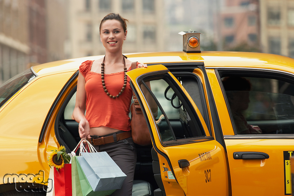 Young woman with shopping bags exiting yellow taxi cab