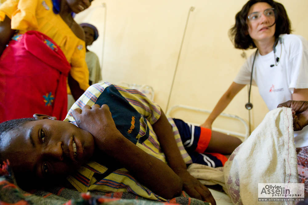 MSF medical doctor Emma Manfrin (right) checks on Issoufou Abdoul Wahab, 17, at the Aguie government hospital in the town of Aguie, roughly 80 km east of Maradi, Niger on Friday April 17, 2009. Issoufou was in coma for three days after being infected with meningitis. He's now on his way to recovery, but is suffering partial loss of hearing - an effect of meningitis that may go away, or not.