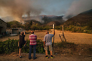 "People watching fires spreading in distance. Orange sky and clouds of smoke looming over the National Park as wildfires sweep through Central Italy. Last summer eight wildfires raged through the area of ""Majella National Park"" in Abruzzo (Central Italy). Fire brigades and groups of volunteers from civil defense have been working on the site for twenty days to stop the flames spreading. Fire has ripped through the National Park destroying swathes of land, up to one-thirds of the Park, its rich environment has been reduced to ashes.  ""More than half of all Italy's wildfires are started deliberately, whether by organized crime, building speculators or farmers seeking more land to cultivate"" has said the Italian environmental organization Legambiente."