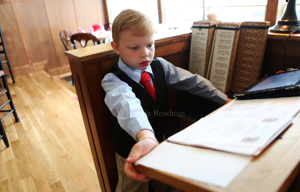 (Falmouth, MA - 5/28/15) Charlie Rickard, 8, who works weekends as a maitre d' in his parents' Falmouth restaurant, Bear in Boots, waits for customers, Thursday, May 28, 2015. He says he is better on the computer than his mom, so he is able to update the tables quickly, and he enjoys talking with people. Staff photo by Angela Rowlings.